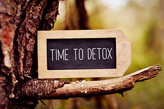 Someone looks at a sign telling them it's time to detox from alcohol and enter rehab to begin their path to recovery.
