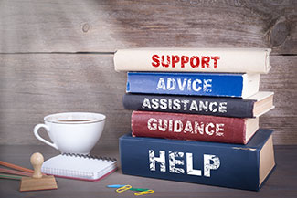 Books on guidance, assistance and advice sit in front of someone seeking alcohol addiction treatment