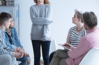 an alcoholic is surrounded by loved ones at an intervention to discuss rehab and recovery