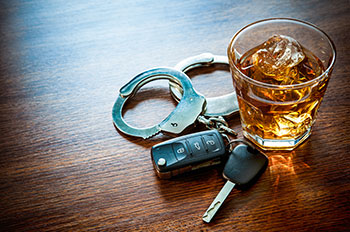 Handcuffs, keys and a scotch sit on a surface after someone made the terrible mistake of getting behind the wheel drunk